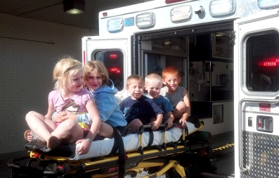 Lacey, Maranda, Elijah, Gage and Andrew enjoy a ride on the ambulance gurney at a daycare in Casper on Wednesday.