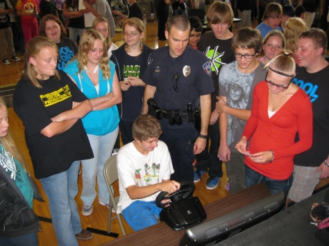 Roosevelt High School students watch one student try out the driving simulator as he tries to not hit a deer or a pedestrian while texting and driving.