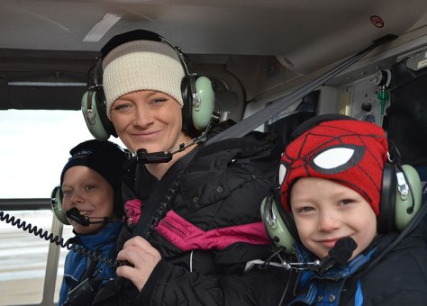 Dorian Layton (at right), his mother Krishelle, and his brother Julien pose for a photo before their helicopter right with Wyoming Life Flight vendors Air Methods. The Air Methods crew gave the Laytons a 20-minute flight around Casper to help the family check off an item from Dorian's bucket list.